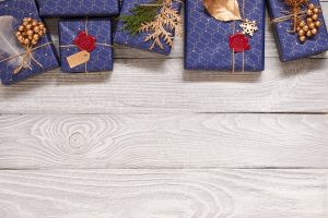 Creatively wrapped and decorated christmas presents in boxes on white wooden background.Top view from above.